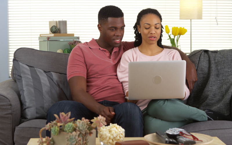 young-african-american-couple-sitting-on-couch-with-laptop-in-lap_4jcbgfmzx__F0000
